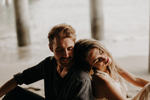 Girl leaning on her fiance's shoulder under Malibu Pier