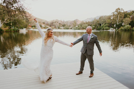 bride in lace dress and groom in grey suit dancing on dock of a lake