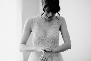 black and white, girl in beaded wedding dress with bangs putting on her bracelet and laughing