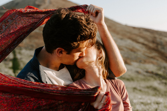 couple kissing with red scarf blowing in the wind