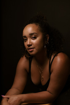black woman with natural hair posing on a stool in photo studio looking seriously at the camera