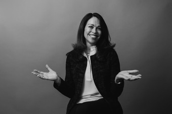 black woman with big smile posing for corporate headshot laughing and holding hands up in the air