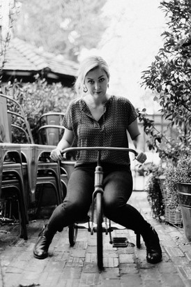 black and white, blonde woman sitting on tricycle making funny face at the camera