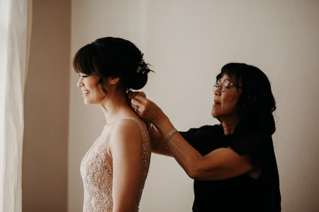 mother of the bride helping daughter in beaded wedding dress put on a necklace