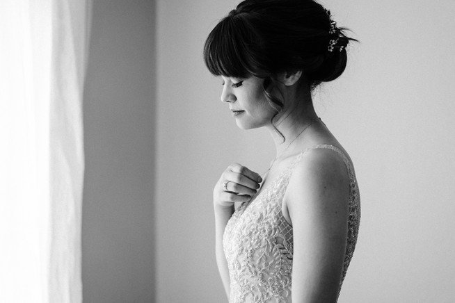 black and white, bride in beaded wedding dress staring out the window and adjusting her necklace