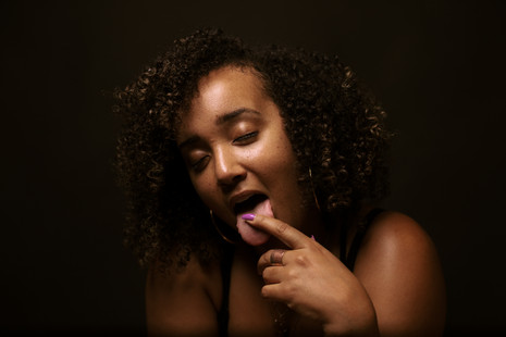 black girl with natural hair and magenta nails touching her tongue with her eyes closed