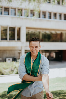 laughing graduate in blue shirt and green sash rolling up sleeves at Cal Poly library
