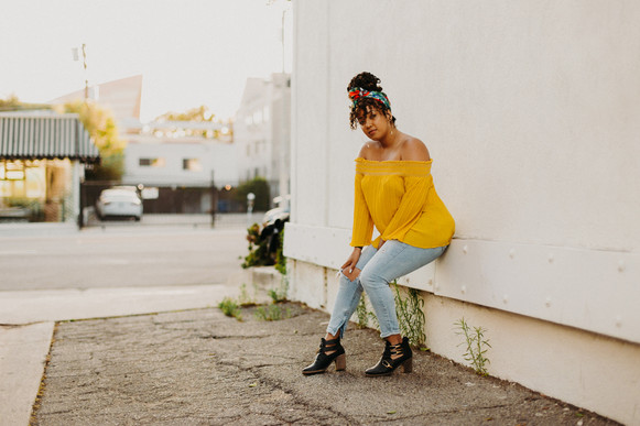young black woman in yellow top and floral headwrap sitting on a wall
