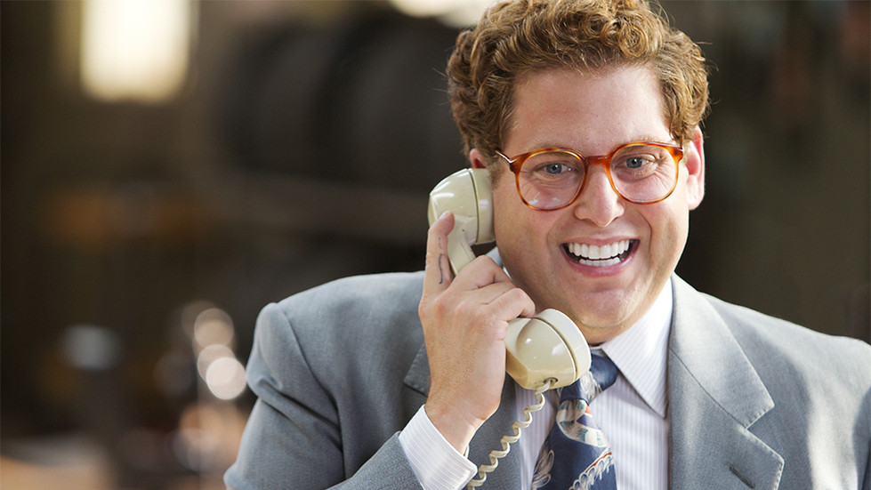 Donnie Azoff from Wolf of Wallstreet taking a phone call with a smile on his face