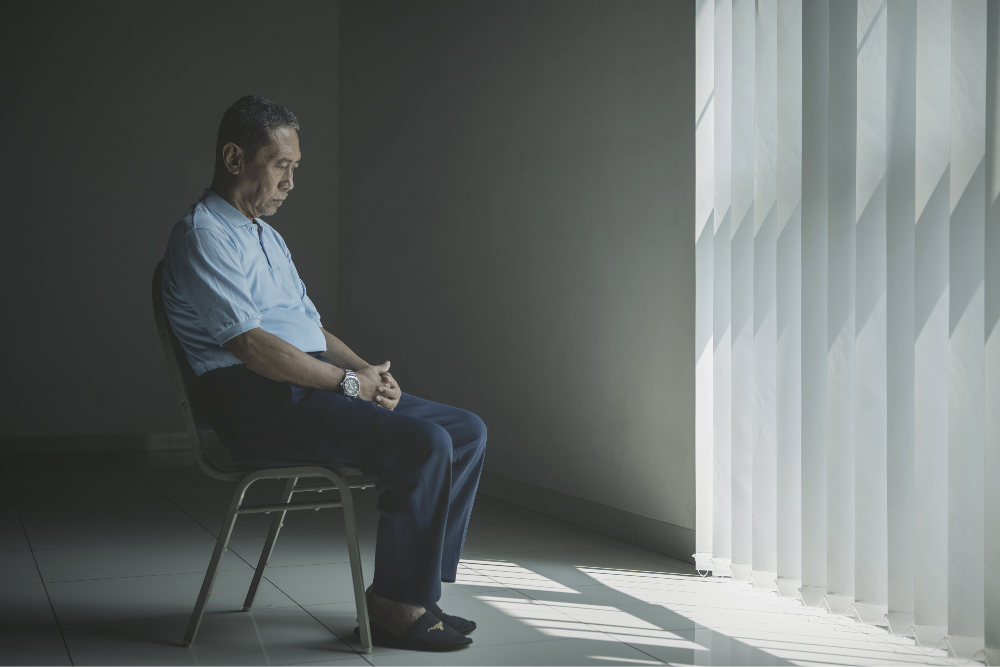 Asian man in front of window in contemplation.