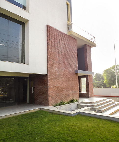 Entrance differentiated not just by exposed brick treatment, but also marked as a transition space with an additional layer or skin; Designed by Designscapes, one of the best Architects in India