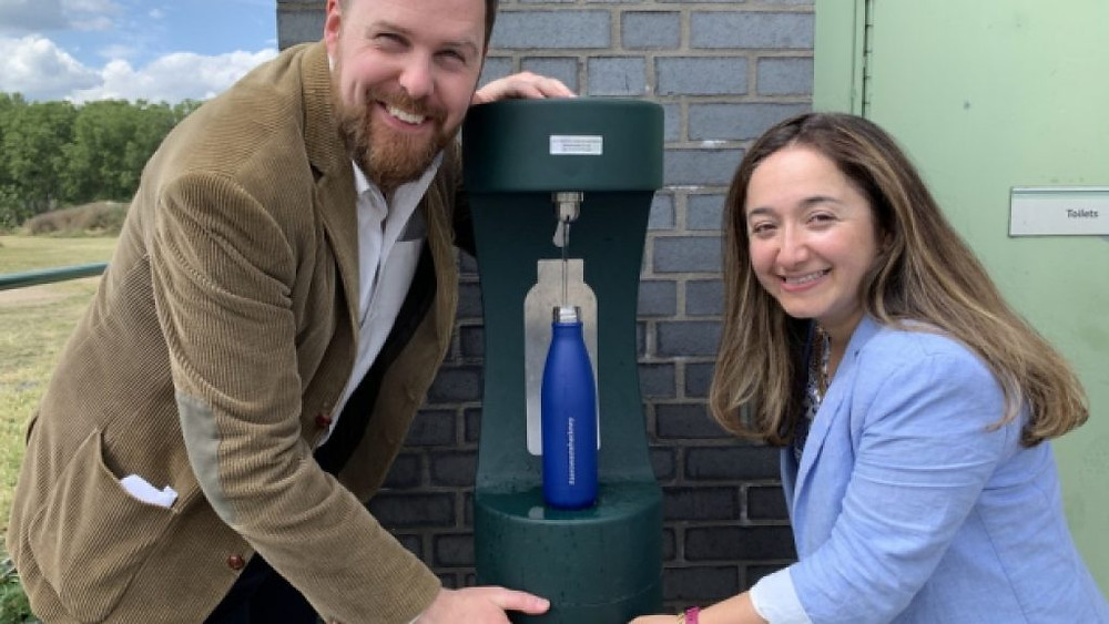 two members of hackney council using a new water fountain and smiling at the camera