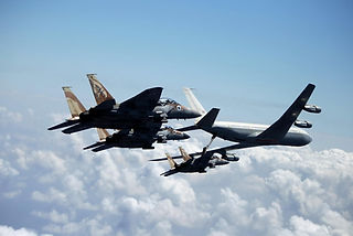 Israeli Airforce Boeing aircraft fueling an F-15 in the air wit two F-15 accompanying the fueling