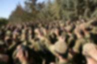 IDF soldiers pray together while usig hands as Kippa outside Lebanon