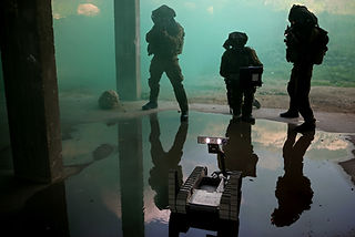 a picture of three combatants from the robotics unit of IDF using a robot inside a building