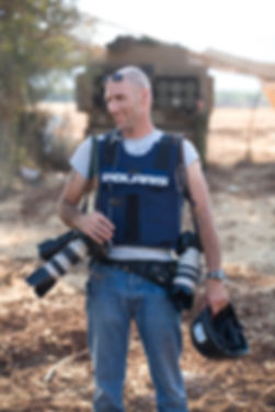 Picture of Israeli Photojournalist Ziv Koren with photography gear and a helmet during a shoot near Gaza