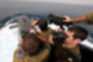 Picture of Israeli Navy officers standing on the bridge of a submarine looking ahead using binoculars