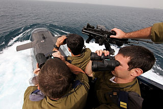 Picture of Israeli Navy officers standing on the bridge of a submarine looking ahead using binoculars