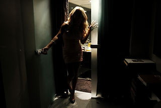 A picture of a tansgender woman coming out from a lit room to a dark room
