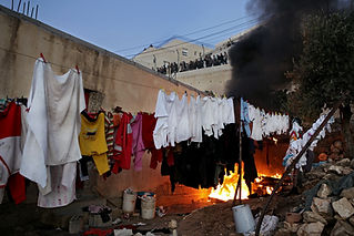 Drying clothes hanging with fire behind in a settlement in Hebron while evacuating the settlement