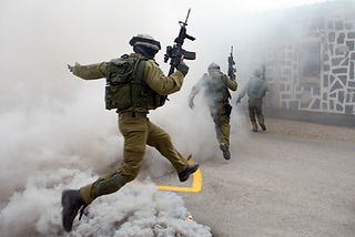 IDF Duvdevan unit combatants in urban combat training running throg smoke