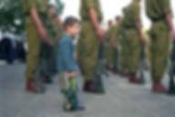 A boy holding a toy gun among IDF Haruv soldiers holding guns