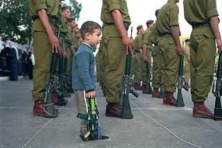 A boy holding a toy gun among IDF Haruv soldiers holding guns