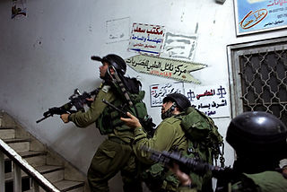 Armed IDF soldiers walk up the stairs of a Palestinian house on their wat o make a arrest of a terror suspect