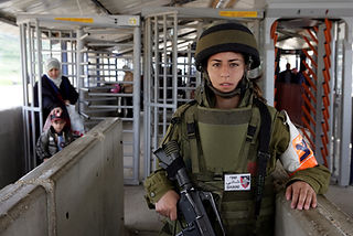 In the picture a woman soldier of the IDF police unit in a border post