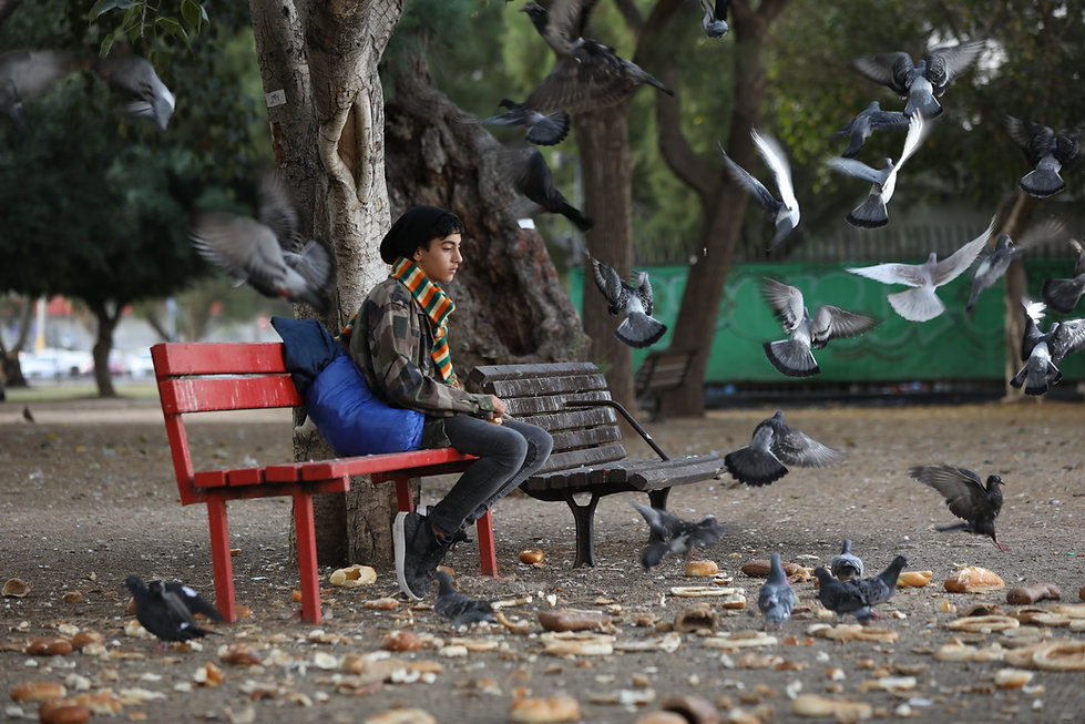 A picture illustrating a homeless teenager sitting on a bench in a park