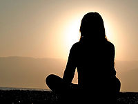 Silhouette of woman sitting down looking at the sun