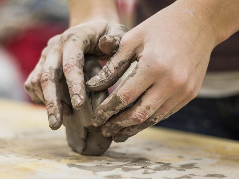 Hands sculpting clay