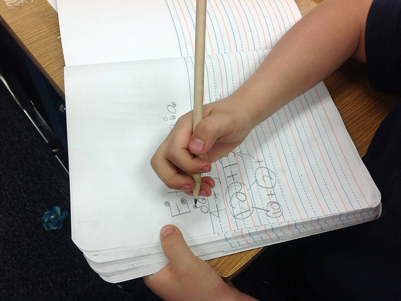 Person writing in a book
