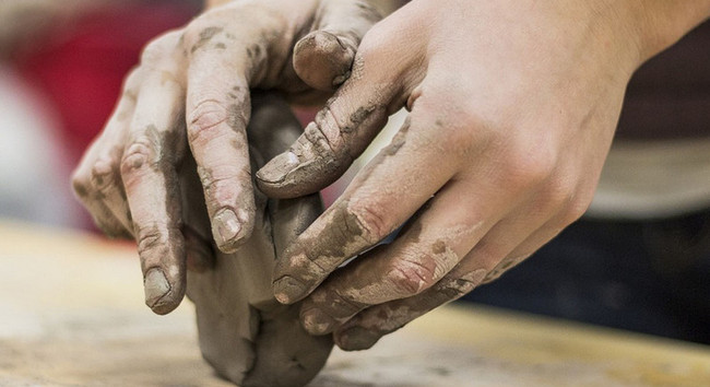 Person making clay sculpture