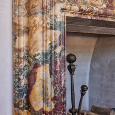 CARVED FROM AN ENORMOUS SOLID BLOCK OF RARE AND BEAUTIFUL STONE, THIS FIREPLACE SURROUND, ALONG WITH ITS ANTIQUE SPANISH ANDIRONS, IS THE FOCAL POINT OF THE WONDERFUL FORTY-FOUR FOOT LIVINGROOM.