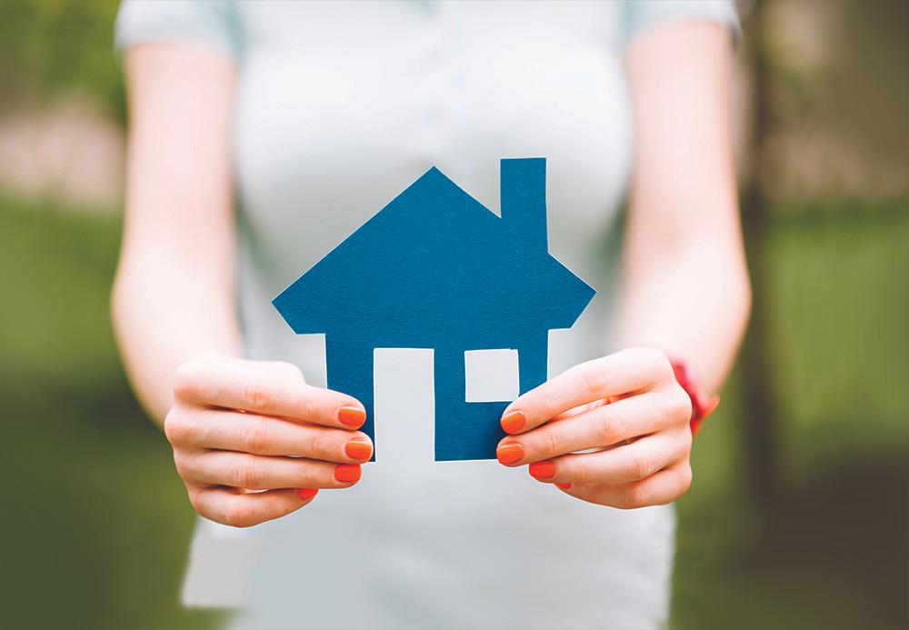 Femme tenant maison en carton