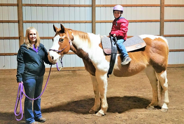 A client recieving equine-assisted therapy in the form of therapeutic riding.