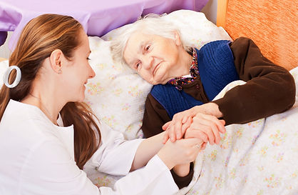 Hospice Care at home for woman laying in bed an being cared for by a provider