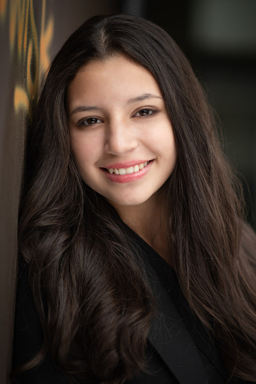 Actress headshot, with a wider smile, closer take, photographed outside using natural light