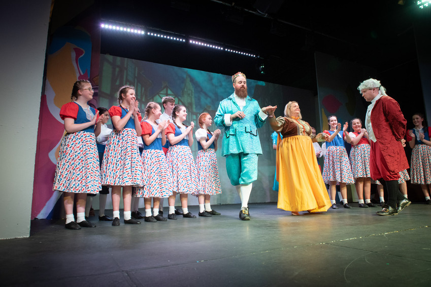 "Photograph Bolton from theatre production of ""Jack and the Beanstalk"" featuring King Crumble and Queen Apricot in front of a choir bowing to the audience."