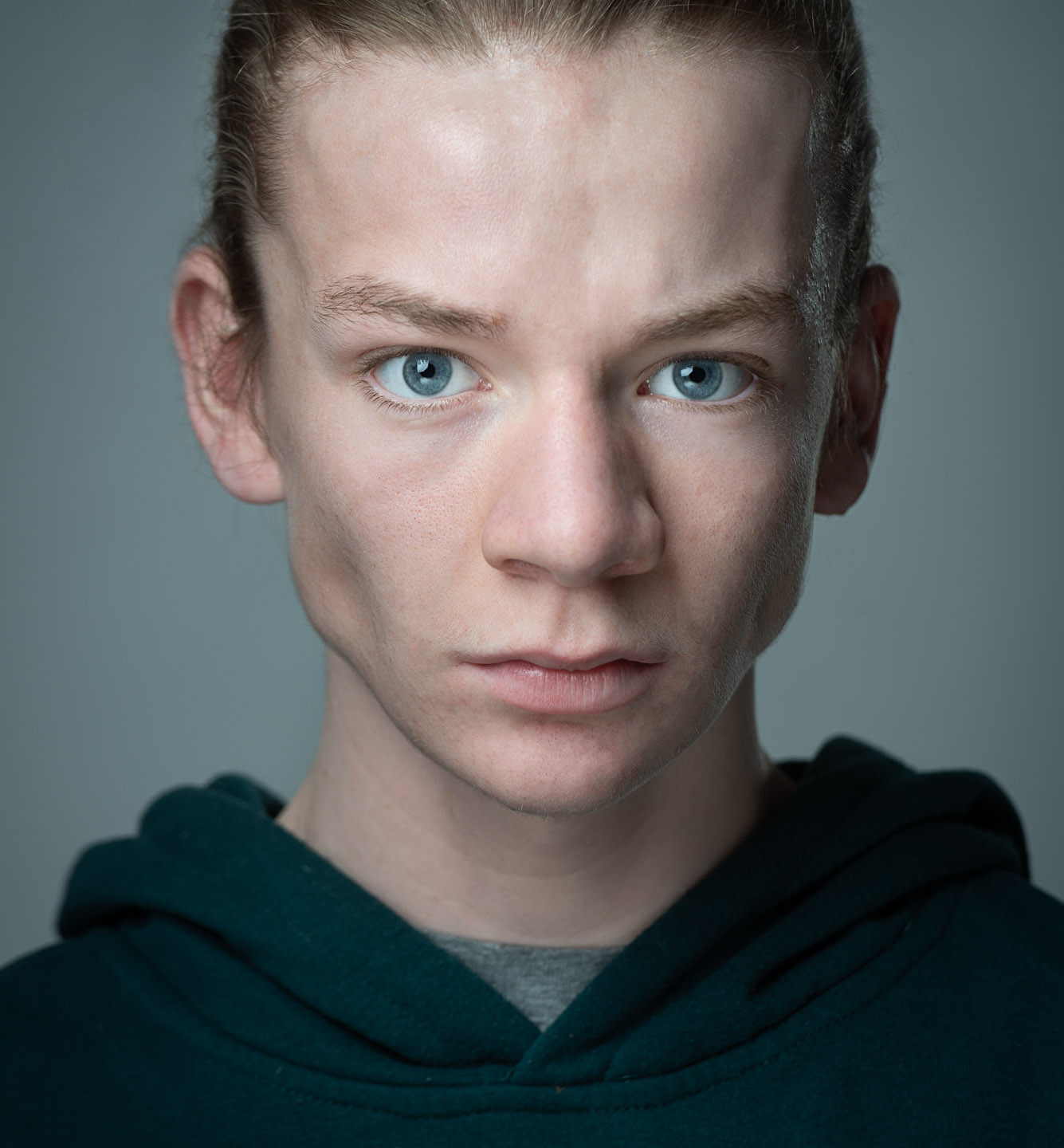 Actors Headshot, intense close up of a young performer with long brown hair tight up behind and blue eyes on light grey dark background