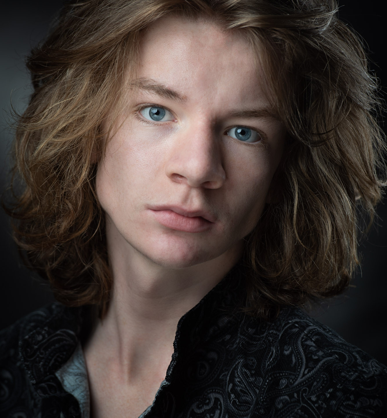 Actors Headshot, moody close up of a young performer with thick long brown hair and blue eyes on dark background
