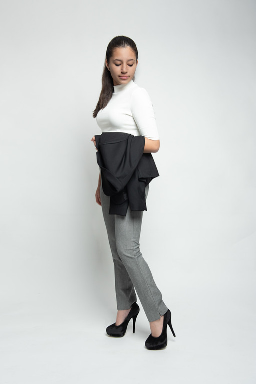 Full length studio portrait photographed on white background in a mid walk position, wearing jeans, black high heels and white polo top holding black jacket