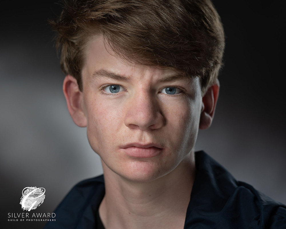 Actors Headshot, intense and moody close up of a young Actor with strong facial features, thick short brown hair and blue eyes on dark background.