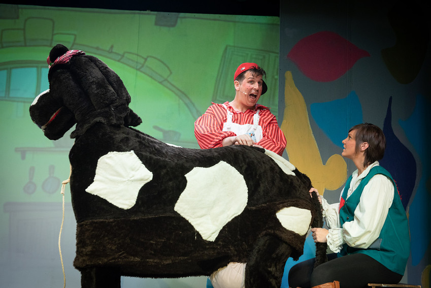 "Close up photograph from Bolton theatre production of ""Jack and the Beanstalk"" featuring Simple Simon and Jack milking their cow Buttermilk."
