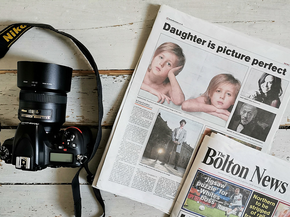 Image of full page article in Bolton Evening News - local paper about top Bolton Portrait Photographer Ania Pankiewicz,  on white wooden floor with a Nikon camera next to it