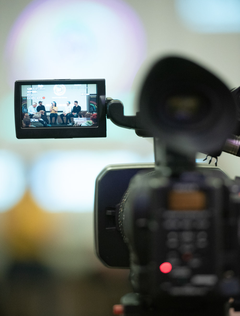 A panel in discussion photographed threw filming camera screen