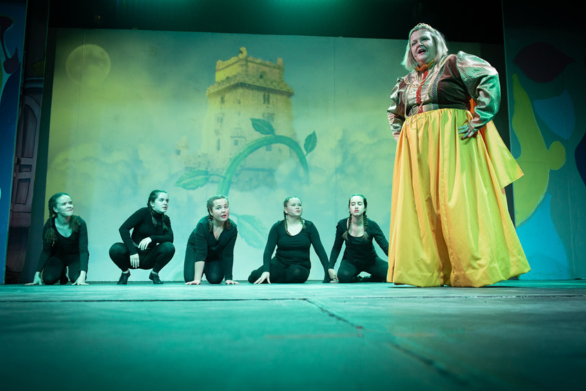 "Photograph Bolton from theatre production of ""Jack and the Beanstalk"" featuring Queen Apricot surrounded by the giant's minions crouching on the floor."