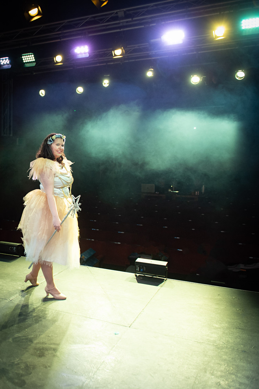 "Photograph from Bolton theatre stage production rehearsals of the ""Jack and the Beanstalk"", featuring fairy Sugardust lone on stage photographed from behind facing empty audience seats with smoke all around her."