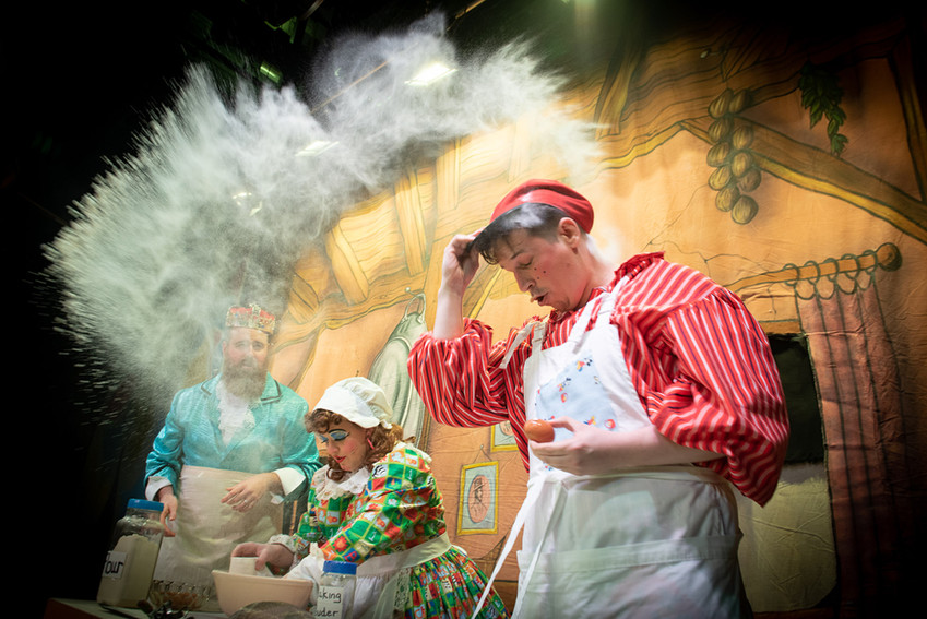 "Image from Bolton theatre production of ""Jack and the Beanstalk"" featuring King Crumble, Dame Dotty Dimple and Simple Simon cooking.  There's flower flying all over the stage as Simon puts his hat on."